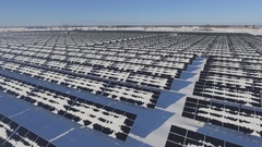 Aerial solar farm low rotating flight in winter showing patterns and sun flare Stock Footage