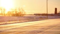 Snow blows across country road and fields Stock Footage