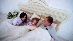 Mom, Dad Wake Daughter Woke Up. Happy Family Lying in White Bedroom Stock Footage