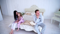 Young Family Quarrel, Husband of Wife and Daughter Sitting on White Bed in Room Stock Footage