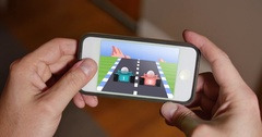 Man Plays Retro 8-Bit Racing Video Game on Smartphone  	 Stock Footage