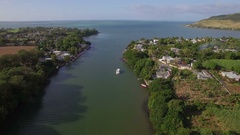 Mauritius coastal town and river falling into ocean, aerial view Stock Footage