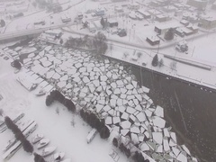 Broken Ice sheets in Small Town River - Snowing Stock Footage