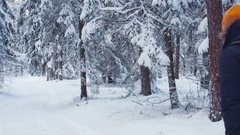HANDHELD Girl pushes tree branch to churn down the snow on a guy Stock Footage