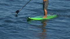 A man surfs on an SUP stand-up paddleboard surfboard. Stock Footage