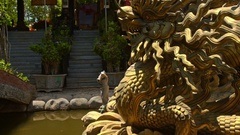 Large Golden Dragon Head Sculpture in Pond Buddhist Temple Park Stock Footage