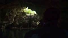 A man with a camera takes a people go down into the cave Stock Footage