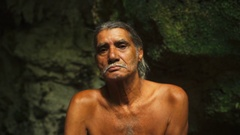 Adult male in shorts sitting on a rock in a cave Stock Footage