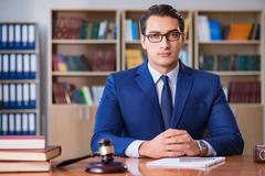 Handsome judge with gavel sitting in courtroom Kuvituskuvat
