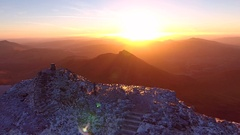Spectacular aerial view of a man and dog on the summit of a mountain at sunrise. Stock Footage