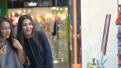 Ladies standing by the shopping window in the mall, emotionally discuss shopping Stock Footage