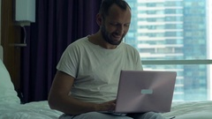 Young man browsing web on laptop sitting on bed at home Stock Footage