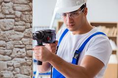 Repairman working with drilling drill perforator Stock Photos