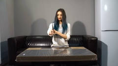 Young cute girl with colored hair sitting on a couch in their new apartment to Stock Footage