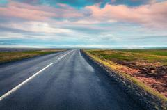Empty asphalt road with colorful cloudy sky. Stock Photos