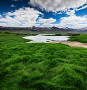 Green grass valley in the volcanic mountains foothill. Stock Photos