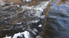 Winter small countryside stream with floating water stones end ice Stock Footage