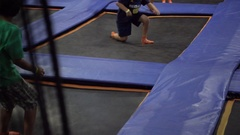 A boy jumps on a trampoline while playing dodge ball, super slow motion. Stock Footage