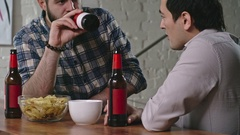 Friends Chatting and Drinking Beer Together Stock Footage