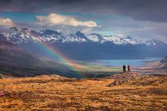 Two photographers takes picture in a light rain and rainbow in the Icelandi.. Stock Photos