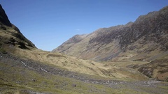 Glencoe Valley mountains in Scottish Highlands and distant traffic Stock Footage