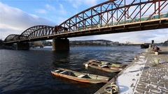 Secured wooden boats on river with train on bridge and flying birds Stock Footage