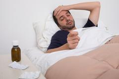 Man feeling bad lying in the bed and controlling the temperature Stock Photos