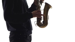 Musician plays an old saxophone. Closeup on white background Stock Footage