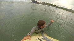 POV of a surfer paddling while surfing to catch a wave, slow motion. Stock Footage