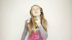 Young girl listening music on headphones holding microphone, singing and funy Stock Footage