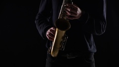 Blues on the saxophone. Musician playing solo in black studio Stock Footage