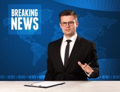 Television presenter in front telling breaking news with blue modern backgrou Stock Photos