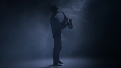 In a dark smoky studio man playing the saxophone Stock Footage