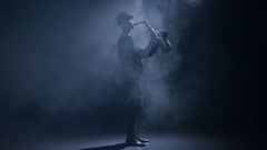 Saxophonist playing a musical instrument in a dark smoky studio Stock Footage