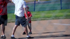 The coach gives a high-five to a boy playing little league baseball. Stock Footage