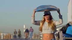 A young woman longboard skateboarding while balancing a surfboard on her head, s Stock Footage