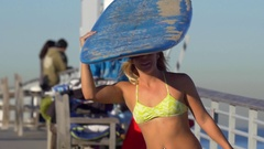 A young woman longboard skateboarding in a bikini while balancing a surfboard on Stock Footage