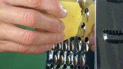 Closeup of a woman grating holand cheese on green background Stock Footage