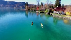 Two kayakers paddle in a scenic mountain lake. Stock Footage