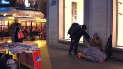 PARIS, FRANCE Poor immigrant sitting on the street. 4K Stock Footage