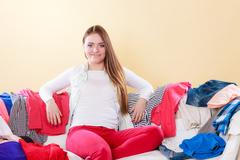 Happy woman sitting on sofa in messy room at home. Kuvituskuvat