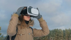 Woman putting on and using virtual reality glasses in winter forest Stock Footage