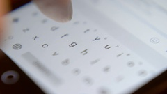 Finger touching virtual keys form a digital keyboard of a touchscreen phone Stock Footage