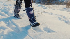 A child runs fun on fresh snow. In the picture can be seen only the legs in Stock Footage