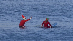 Santa and Mrs. Claus give a high five while sitting on their surfboards waiting Stock Footage