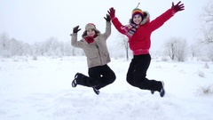 Two kids jumping together on winter landscape, slow motion Stock Footage