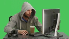Mid Shot of a Hacker Wearing Hoodie Sitting at His Desktop Computer. Shot on Gre Stock Footage