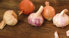 Garlic bulbs and onion on wooden board, natural medicine, eat healthy food Stock Footage
