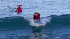 Mrs. Claus goes surfing at the beach. Stock Footage