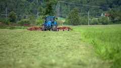 Blue tractor is driving across a large grass field Stock Footage